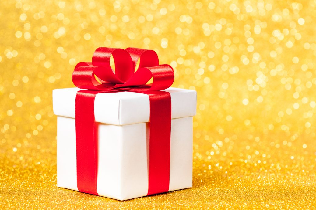 gift box with red ribbon, glittery gold background